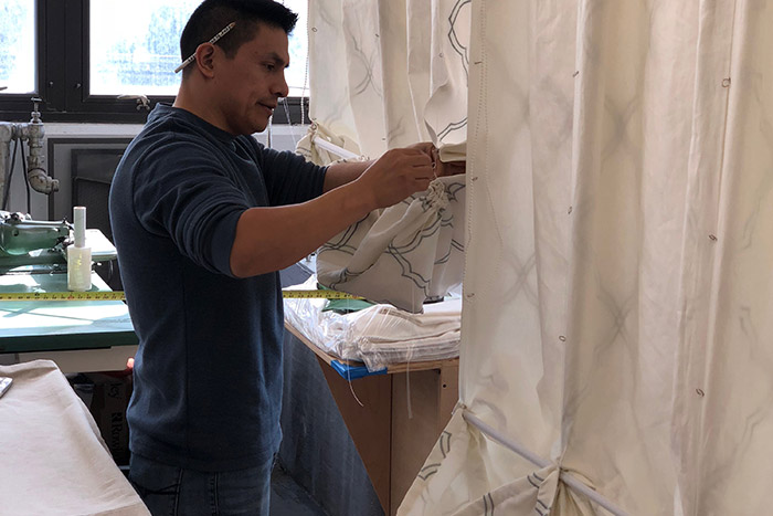 man working on curtains
